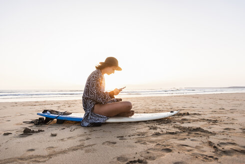 Young woman sitting on surfboard at the beach, using smartphone - UUF15159