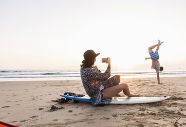 Young woman sitting on surfboard, taking pictures of young man, practicing handstands on the beach - UUF15162