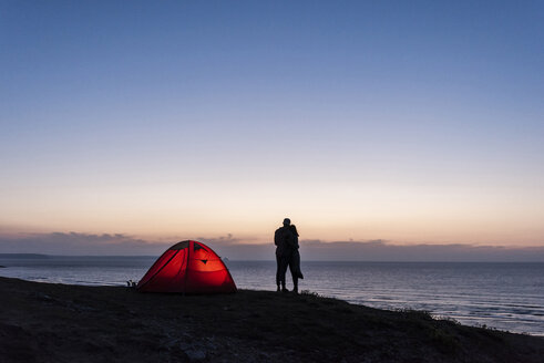 Romantic couple camping on the beach, kissing in twilight - UUF15168