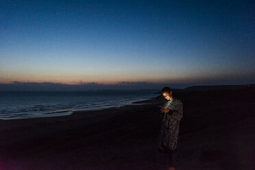 Young woman using smartphone on the beach at night - UUF15174