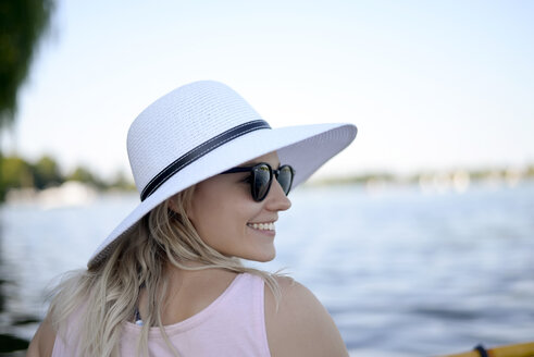 Smiling young woman wearing sunglasses and white summer hat al lake - BFRF01905