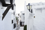 Spain, Menorca, Binibequer, back view of woman walking in an alley - IGGF00585