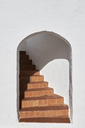 Spain, Menorca, white wall with arch and staircase behind - IGGF00606