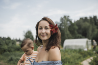 Portrait of mother with flower in her hair with baby in garden - KMKF00548