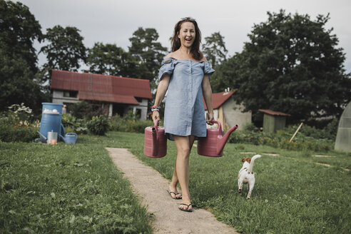 Happy woman with Jack Russel Terrier carrying watering cans in garden - KMKF00554