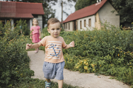 Baby boy walking in garden with sister in background - KMKF00557