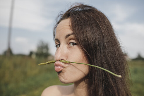 Portrait of woman balancing plant stalk on her mouth - KMKF00560