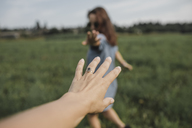 Hand reaching out for woman on a field - KMKF00563