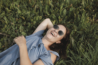 Laughing woman wearing sunglasses lying in grass - KMKF00569