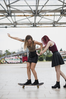 Young woman pushing friend on skateboard in the city - MAUF01679