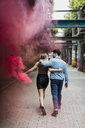 Young couple with smoke torch walking outdoors - MAUF01697