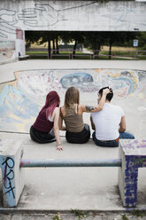 Rear view of friends sitting in skatepark - MAUF01706