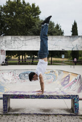 Young man doing a handstand on bench in skatepark - MAUF01709