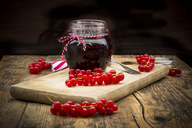 Jam jar of currant jelly and red currants on wooden board - LVF07415