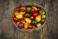 Basket of Heirloom tomatoes on wood - LVF07418