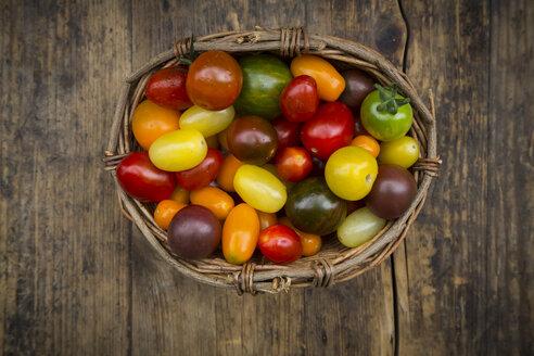 Basket of Heirloom tomatoes on wood - LVF07418