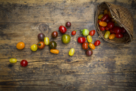 Heirloom tomatoes and wickerbasket on wood - LVF07421