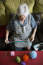 Senior woman crocheting on the couch at home, top view - RAEF02135