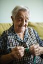 Portrait of smiling senior woman crocheting on the couch at home - RAEF02138