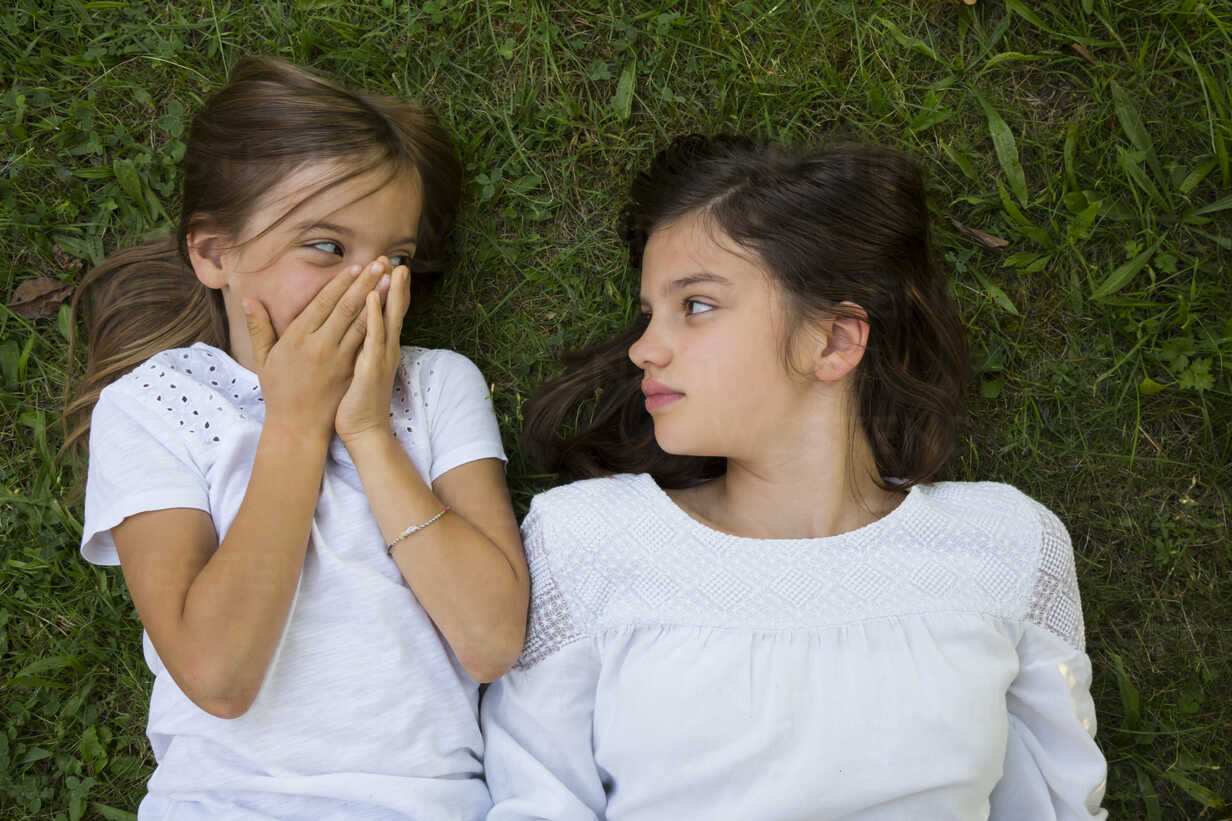 Two sisters lying together on a meadow - LVF07438 - Larissa Veronesi/Westend61