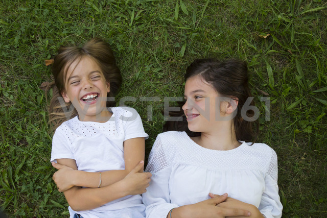 Two sisters lying together on a meadow having fun - LVF07441