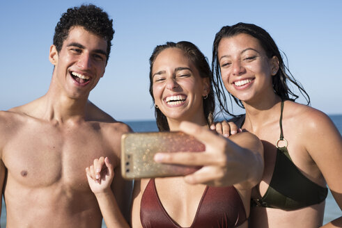 Happy friends taking selfies on the beach - PACF00091