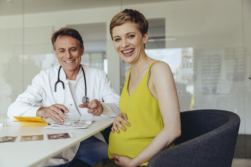 Pregnant woman discussing ultrasonic scans with her doctor - MFF04470