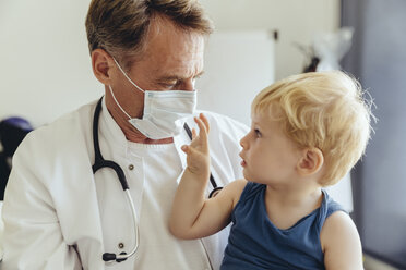 Toddler sitting on lap of pediatrician, wearing protective mask - MFF04476