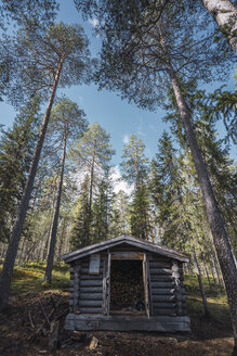 Finland, Vikakongas, Wooden barn with fire wood in forest - KKAF01695