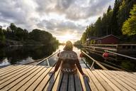 Finland, Kajaani, Man sitting on jetty, watching sunset, rear view - KKAF01710