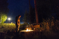Finland, Man warming up at a camp fire on a camping ground - KKAF01728