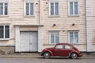 Finland, Porvoo, Red vintage car in front of house facade - KKAF01740