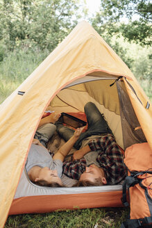 Young couple relaxing in tent, using digital tablet - VPIF00621