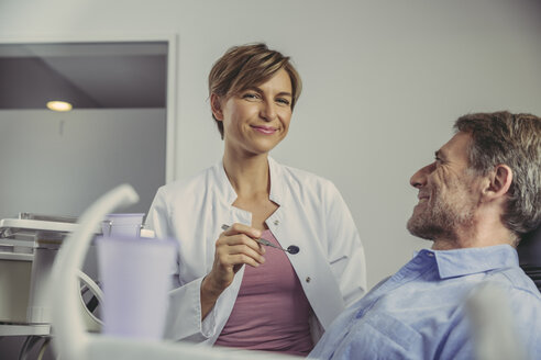 Female dentist talking to her patient before treatment - MFF04518