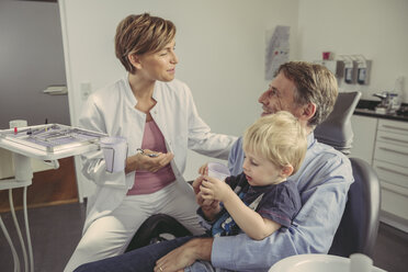 Female dentist talking to patient with son sitting on his lap - MFF04521