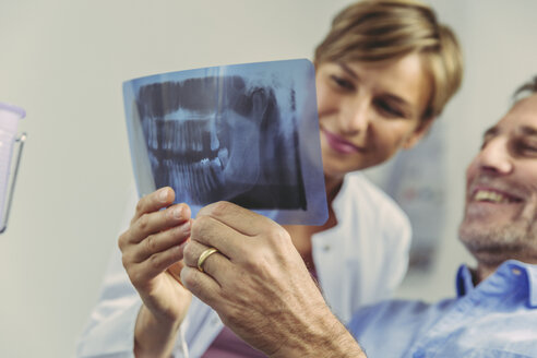 Dentist explaining x-ray image to smiling patient - MFF04542