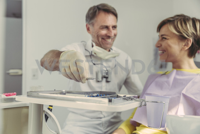 Dentist putting instruments on tray after treatment, looking at his smiling patient - MFF04563 - Mareen Fischinger/Westend61