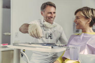 Dentist putting instruments on tray after treatment, looking at his smiling patient - MFF04563
