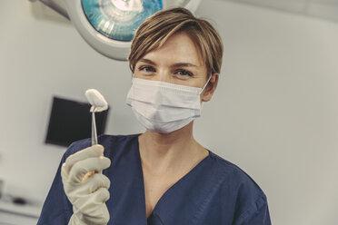 Dental surgeon wearing surgical mask, holding swab - MFF04581