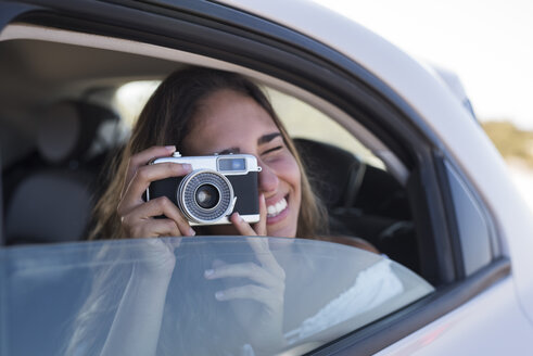 Woman sitting in car, taking pictures with a camera - PACF00101