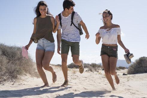 Friends having fun, running barefoot on the beach - PACF00119