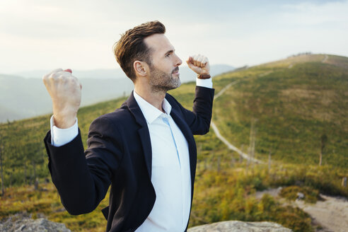 Self-confident businessman standing on top of a mountain - BSZF00582