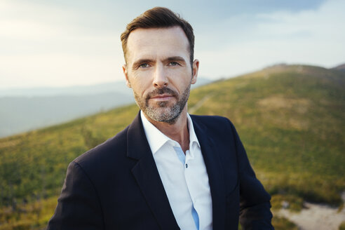Portrait of self-confident businessman  on top of a mountain - BSZF00585