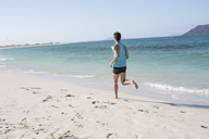 Spain, Canary Islands, Fuerteventura, rear view of young man running on the beach - PACF00136