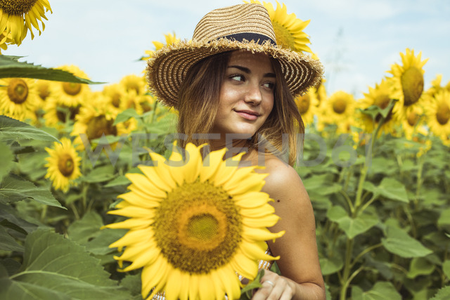 Young woman with a straw hat smiling in a field of sunflowers - ACPF00329 - Aitor Carrera Porté/Westend61