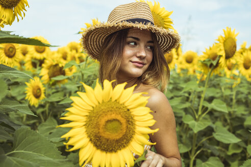 Young woman with a straw hat smiling in a field of sunflowers - ACPF00329