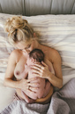 Newborn baby lying skin to skin with mother in bed - MFF04588