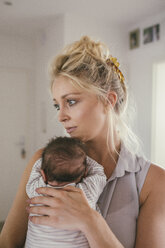 Mother holding her baby at home - MFF04609