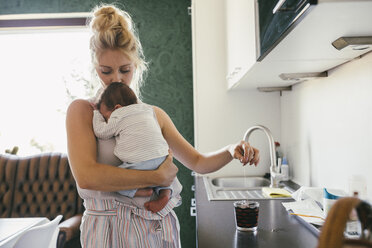 Mother holding newborn baby in kitchen while making tea - MFF04612