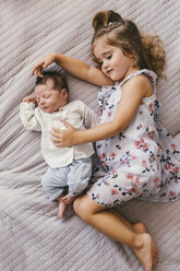 Girl lying on blanket cuddling with her baby brother - MFF04615